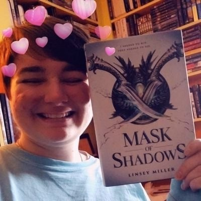 Avery using a snapchat filter to put in animated hearts above their head. They are wearing a light blue, long sleeve shirt, and holding up a hardcover copy of Linsey Miller's Mask of Shadows near their face.